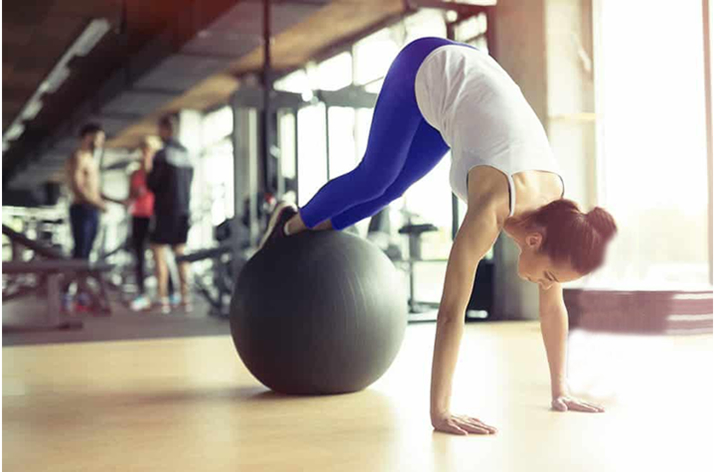 woman doing pilates exercise with ball