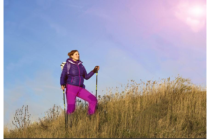 woman walking up hill with walking poles